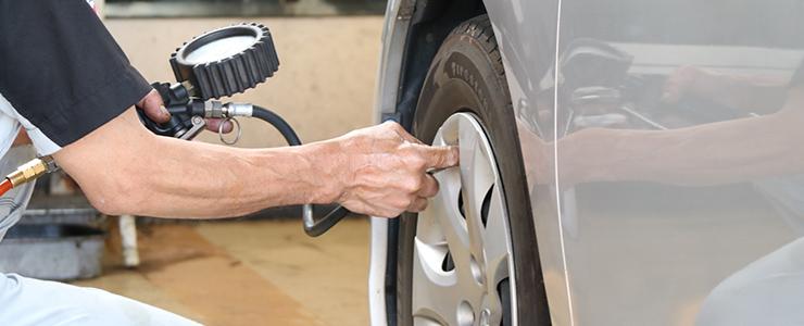 タイヤの空気圧を計って適正値にする男性